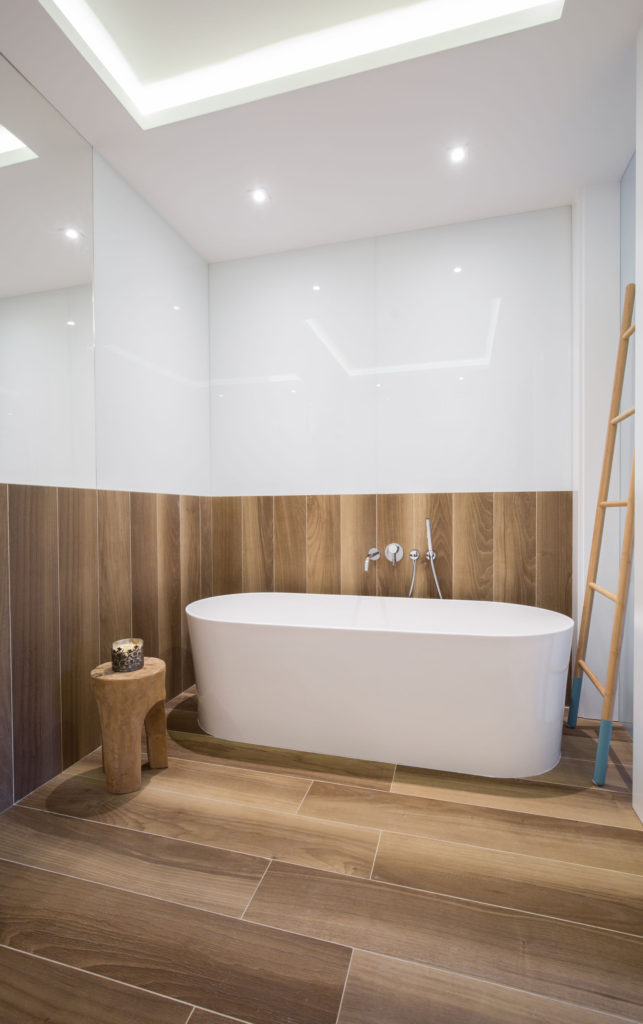 41635587 - cozy wooden bathroom with white porcelain bathtub